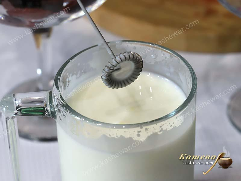 Kefir in a glass with a whisk.