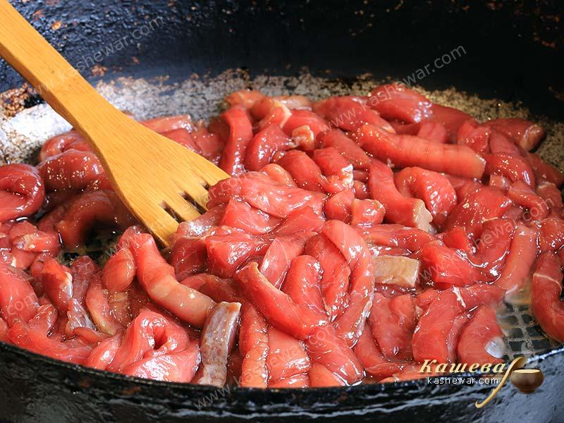 Beef, cut into strips, in a frying pan