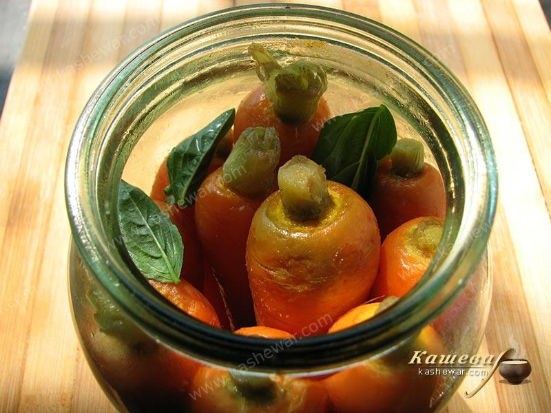 Placing pickled carrots in jars