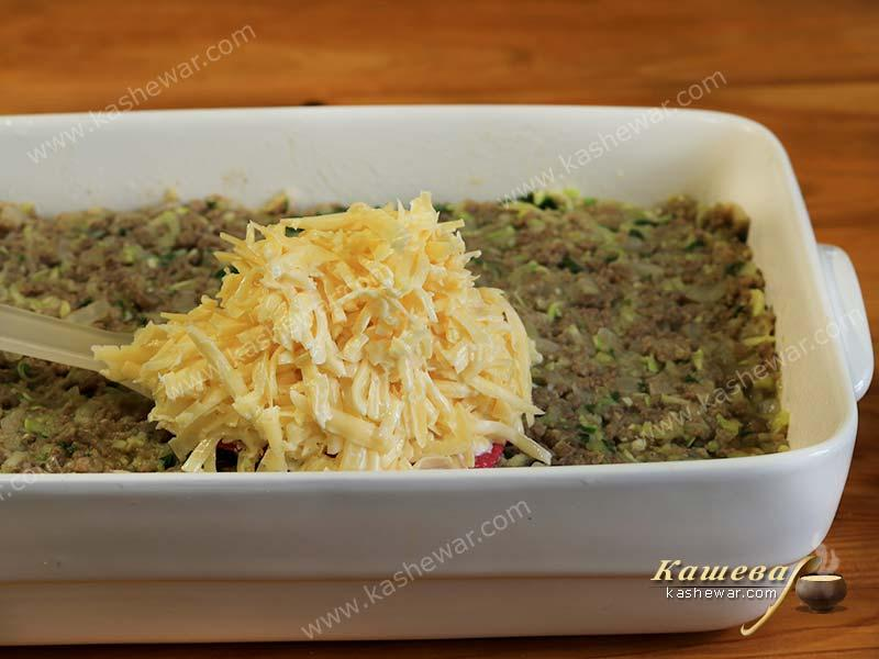 Grated cheese is laid out on top of minced meat