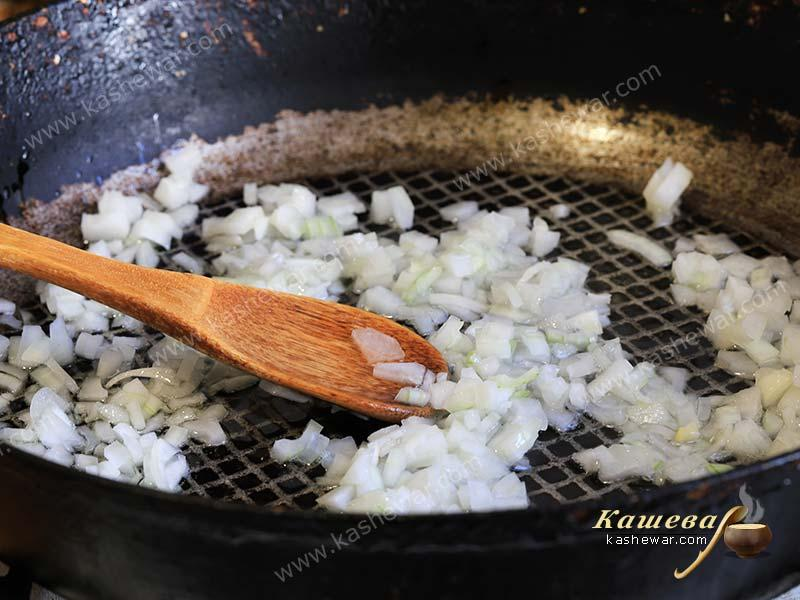 Finely chopped onions in a frying pan with olive oil